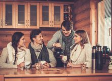Young couples drinking hot tea in winter cottage kitchen. Royalty Free Stock Photos