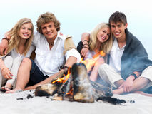 Young couples enjoying bonfire at beach in summer Royalty Free Stock Image