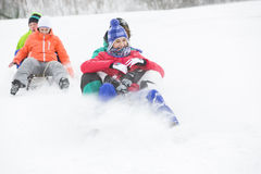 Young couples enjoying sled ride on snow covered slope Stock Photography