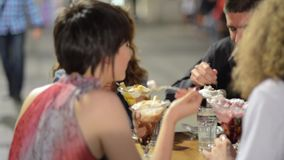 Young couples enjoying some food and drinks stock footage