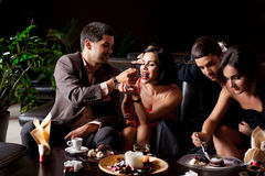 Young couples having deserts and coffee Stock Images