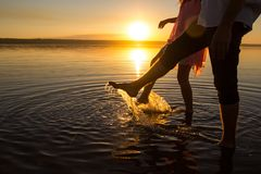 Free Young Couples Is Walking In The Water On Summer Beach. Sunset Over The Sea.Two Silhouettes Against The Sun. Feet Doing Splashes Of Stock Images - 144936874