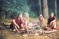 Young couples in love having picnic in woods, double date. Bearded man and his friend frying sausages over campfire royalty free stock photos