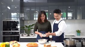 Young couples making bakery. Asian couple cooking together at the kitchen.
