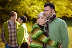 Young couples outdoor at autumn. Young love couples hugging and walking in park outdoor at autumn, smiling Stock Photos