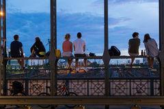 Young couples on romantic date on urban railway bridge, Munich, Germany. Young couples in love on romantic date sitting on railway bridge with a bottle of wine royalty free stock image