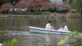 Young couples row boats in autumn Ueno park stock footage