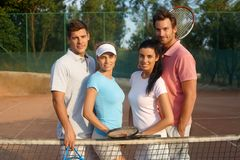 Young couples on tennis court smiling. Young couples standing on tennis court, smiling Stock Image