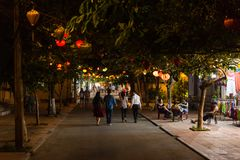 Young couples walking in the streets of Hoi An during warm summer evening. HOI AN, VIETNAM - OCTOBER 2014 - Young couples walking in the streets of Hoi An during royalty free stock photo