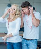 Young Couples on White Blue Attire Listening Music Royalty Free Stock Images