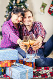 Young couplr with goblets of champagne wine under christmas tree stock images