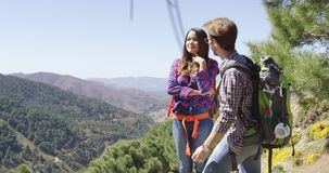 Young coupole having fun in mountains. Young couple hiking in mountains with backpacks and man pointing away with beautiful view on background stock footage