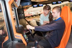 Young coupple playing driving wheel video game in game room royalty free stock photo
