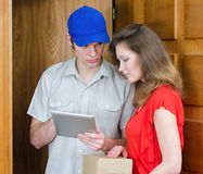 Young courier deliver package. To pretty woman Stock Image