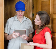 Young courier deliver package. To pretty woman Royalty Free Stock Photo