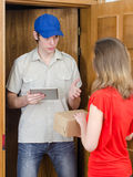 Young courier deliver package. To pretty woman Royalty Free Stock Image