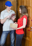 Young courier deliver package. To pretty woman Royalty Free Stock Photography