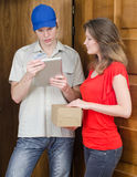 Young courier deliver package. To pretty woman Stock Photography
