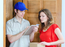 Young courier deliver package. To pretty woman Stock Images