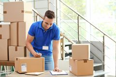 Young courier making notes on parcels at delivery department stock images