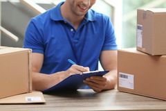 Young courier working with papers among parcels at table. In delivery department stock photos