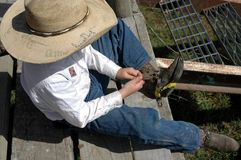 Young cow boy. Young cowboy fitting spurs royalty free stock photography
