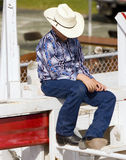 Young Cowboy. A young cowboy sitting on a fence during rodeo Stock Image