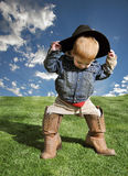 Young Cowboy. A young child wearing a black cowboy hat and crocodile skin boots, outside on a sunny day Royalty Free Stock Photo