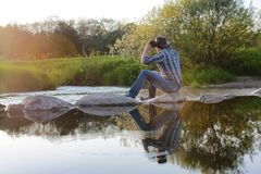 Young cowboy admires the sunset in the spring evening on the riv stock photo