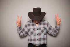 Young cowboy against a green background. A young cowboy wearing a plaid shirt is posing against a green wall Stock Image