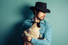Young cowboy with cat is smoking Stock Photos