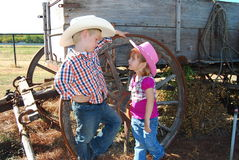 Child cowboy and cowgirl. Young cowboy and cowgirl standing by a wagon royalty free stock image