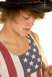 Young cowboy in flag tank top close. A young cowboy with a rope over his shoulder looking down Royalty Free Stock Photo