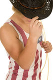 Young cowboy in flag tank top hold hat down. A young cowboy touching the brim of his hat, and holding on to his rope Stock Photo