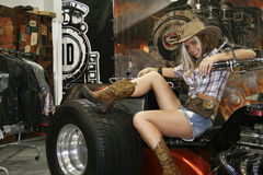 Young cowboy girl posing on a motorcycle Royalty Free Stock Photos