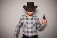 Young cowboy with a gun. A young man wearing a cowboy hat and a plaid shirt is holding a revolver Stock Photo
