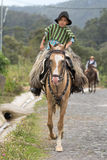 Young cowboy on horse back. May 27, 2017 Sangolqui, Ecuador: young cowboy on horse back wearing chaps riding to a rural rodeo in the Andes Stock Photo