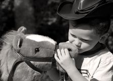 Young cowboy kissing his horse. Young boy dressed as cowboy giving toy horse a kiss Stock Images