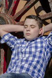 Young cowboy lying beside a wagon wheel Stock Images