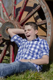 Young cowboy lying beside a wagon wheel Stock Photography