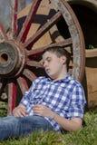 Young cowboy lying beside a wagon wheel Stock Photo