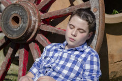 Young cowboy lying beside a wagon wheel Royalty Free Stock Images