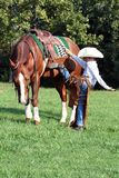 Young cowboy mounting horse. A young cowboy mounting his saddled horse Royalty Free Stock Photography