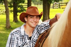 Young Cowboy and Palomino. Portrait of a young man with a cowboy hat and Palomino horse Royalty Free Stock Photo