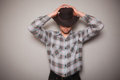 Young cowboy in plaid shirt against a green wall Stock Photos