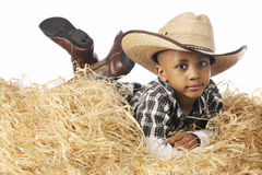 Young Cowboy Relaxing in the Straw. A young African American cowboy relaxing in a pile of straw.  On a white background Stock Images