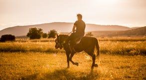 Man Riding Horse at sunset Royalty Free Stock Photos