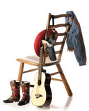 A Young Cowboy's Gear. On or near a ladderback chair: boots, guitar, hat, gun in holster and a denim jacket.  Isolated on white Stock Photography