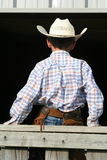 Young cowboy sitting on fence. Young cowboy sitting on a fence rail facing away Stock Photo