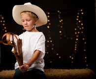 Young cowboy sitting on hay bale with his stick horse. Young caucasion boy wearing white tee shirt and cowboy hat holding stick horse and sitting on hay bale day royalty free stock photo